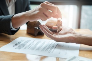 estate agent giving house keys to man and sign agreement in office